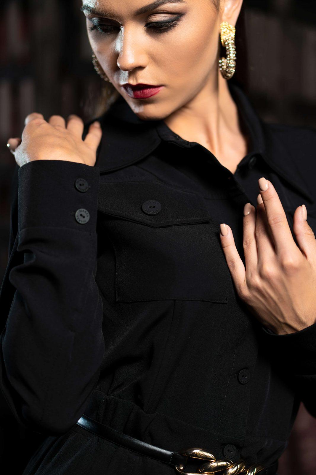 Къса елегантна черна рокля с копчета и волан. Изработена е от нежна материя, която се спуска свободно по тялото. Универсален модел, който е подходящ за всякакъв повод.