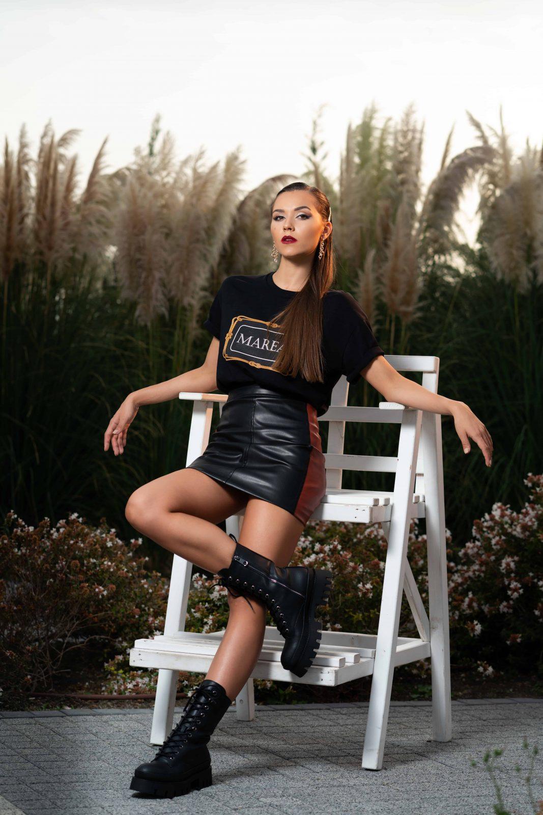 Черна, ултра-модерна тениска и черна къса пола над коляното